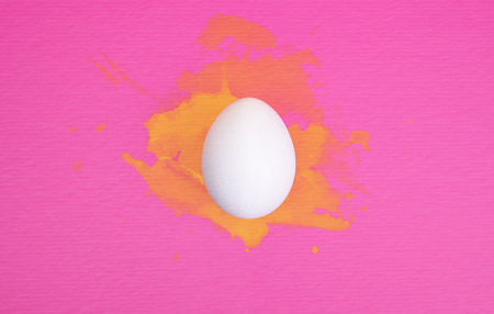 One white egg on bright pink background with yellow watercolor splatters.
