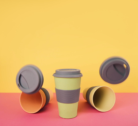 Take away coffee cups on colorful paper background.