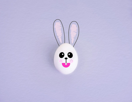 One white egg painted as a rabbit on pastel lilac background.