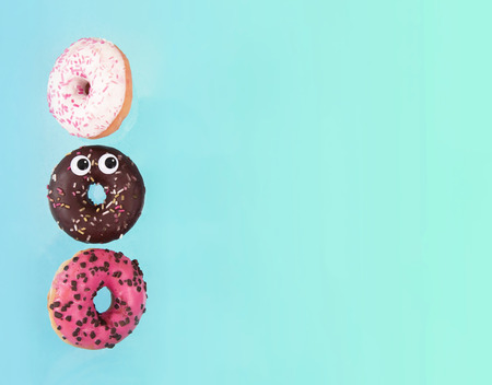 Colorful glazed donuts in motion with funny eyes.