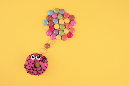 Colorful glazed donuts with funny eyes on yellow background.