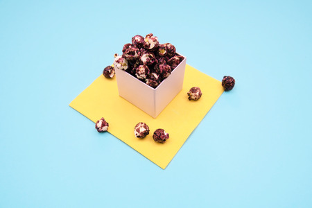 Pink popcorn with berry taste in paper cup on blue and yellow background.