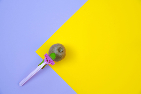 Kiwi fruit and razor on violet and yellow background. Hair removal concept.