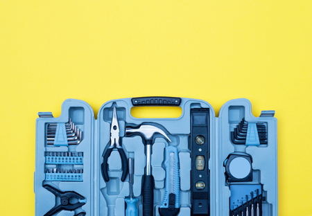 Toolbox set of tools. Home improvement concept on yellow background.