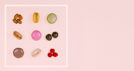 Colorful macaroons on the pastel pink background.