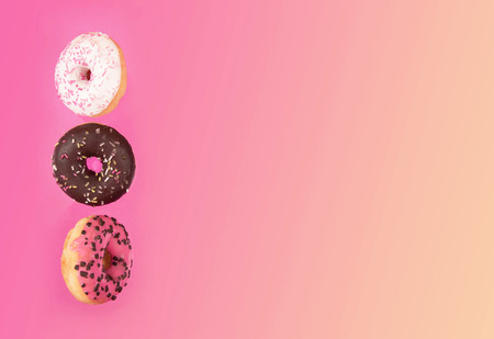 Colorful glazed donuts in motion on pink background.