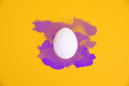 One white egg on bright yellow background with violet watercolor splatters. Stock Photo