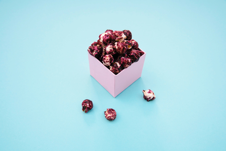 Pink popcorn with berry taste in paper cup on blue background. Stock Photo