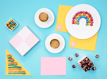 Colorful still life with sweets and present on blue background. Stock Photo