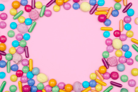 Round frame with assorted colored candies on pink background.