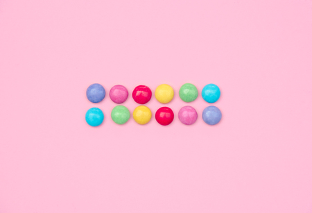 Assorted colored candies on pink background. Stock Photo