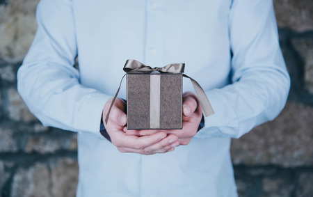 Male hands holding a gift.