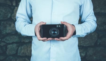 Hands holding retro camera.