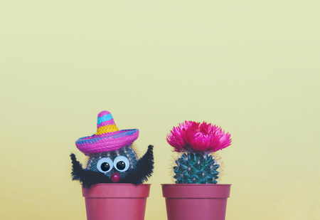 Two small cactuses in a flowerpot on a trendy yellow background.