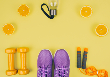 Flat lay shot of sneakers, dumbbells, jump rope.