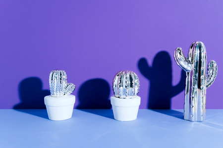 Creative golden cactus on ultraviolet background.