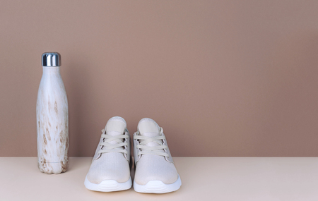 Shot of golden sneakers on beige background. Stock Photo