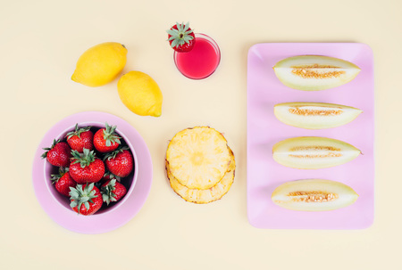 Fresh strawberries in bowl and melon on pastel yellow background. Top view point.