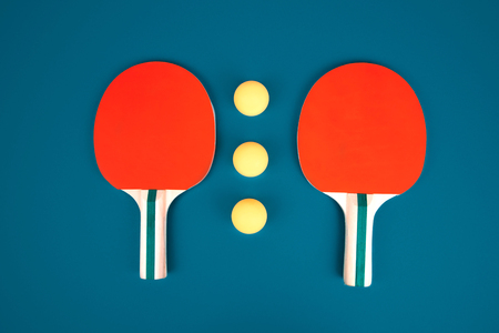 Table tennis or ping pong rackets and balls on a blue table. Foto de archivo