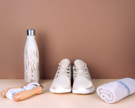 Shot of golden sneakers on beige background. Stylish healthy lifestyle concept.