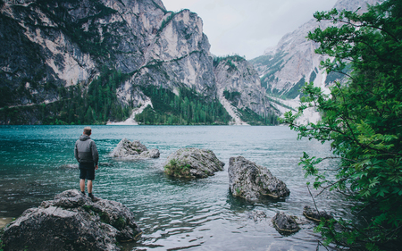 Hiker enjoing beautiful view of Lago di Braies or Pragser wildsee, Trentino Alto Adidge, Dolomites mountains, Italy.