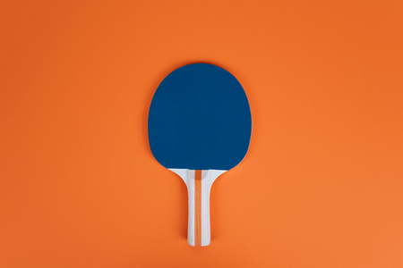 Table tennis  racket on an orange table.