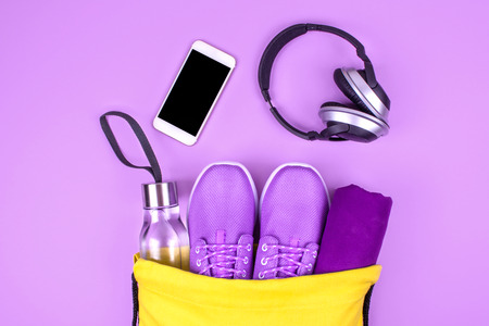 Creative flat lay of sport and fitness equipments on violet background with copy space.