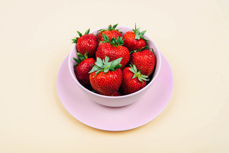 Fresh strawberries in bowl on pastel yellow background.