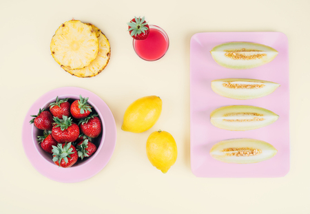 Fresh strawberries in bowl and melone on pastel yellow background. Top view point.