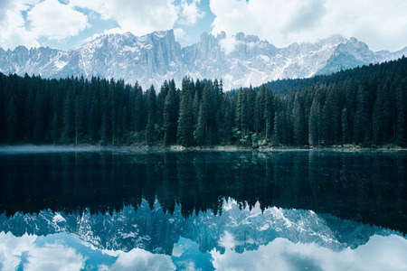 The Karersee lake or Lago di Carezza with reflection of mountains in the Dolomites, South Tyrol, Italy.