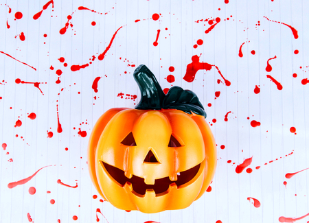 Halloween pumpkin head lantern on a white background covered with blood.