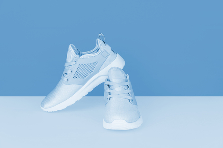 Shot of silver sneakers on blue background. Stylish healthy lifestyle concept. Kho ảnh