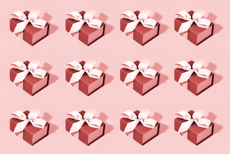 Pattern made of red gift boxes on pastel background.