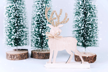 Christmas wooden tree with reindeer over light blue background. Xmas and holiday concept.