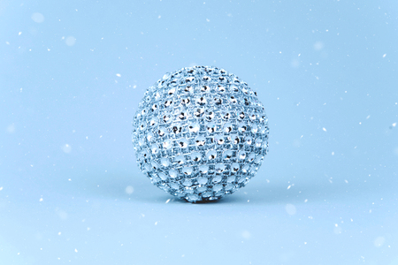 Silver shiny Christmas bauble decoration on pastel blue background. New Year party background.