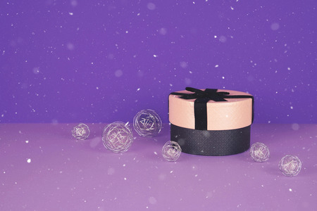 Pink gift box with ribbon on an ultraviolet background with copy space.
