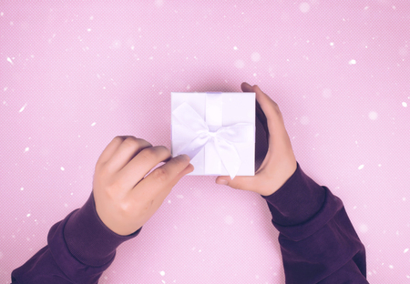Top view of hands holding a small box with a gift and a ribbon on a blue background. Stock Photo