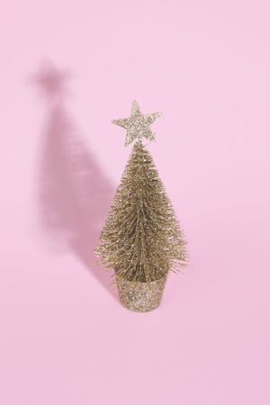 Christmas tree over light pink background. Xmas and holiday concept. Stock Photo