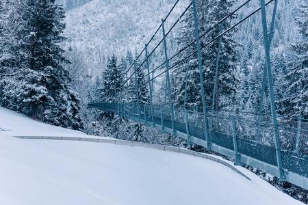 Pedestrian suspension bridge in Sattel Lucerne region Switzerland. Winter landscape.