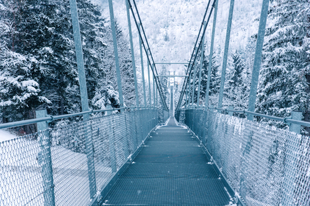 Pedestrian suspension bridge in Sattel Lucerne region Switzerland. Winter landscape.