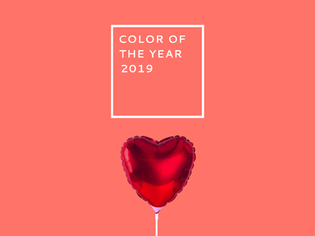 Red heart balloon isolated on Living Coral background. Color of the year 2019.