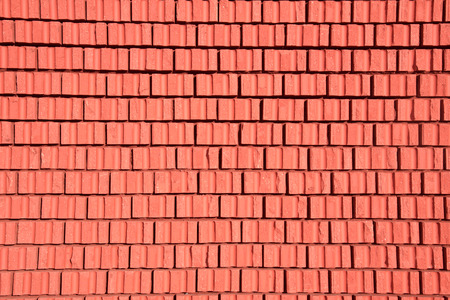 Brick wall texture of red stone blocks closeup as a background. Color of the year 2019. Stock Photo