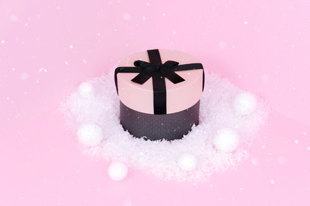 Pink gift box with ribbon on an pink background.