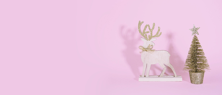 Christmas wooden tree with reindeer over pink background. Xmas and holiday concept.