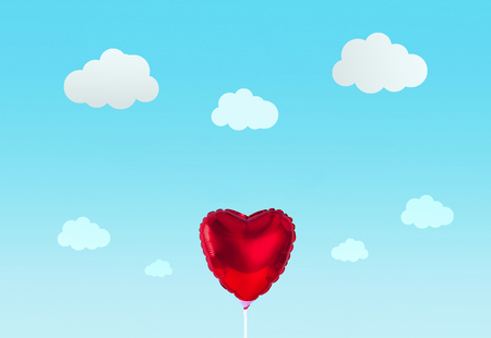 Red heart balloon isolated on blue background. Creative minimal love concept.