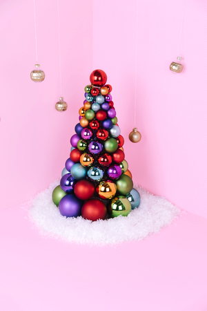 Christmas tree made of pink decoration on pink background. Xmas and holiday concept.