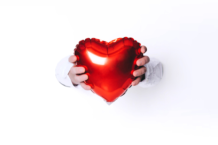 Hands holding a heart on white background. Creative minimal concept.