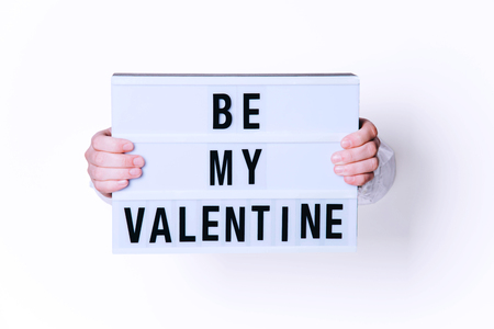 Male hands with Be My Valentine sign on white background. Minimal art style.