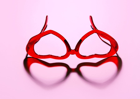 A pair of red heart shaped sun glasses on pink background. Stock Photo