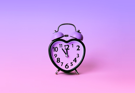 Heart shaped clock on pink background. Valentines day and love and duration concept. Banco de Imagens